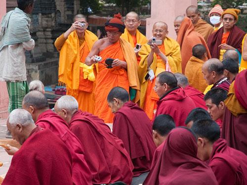 チベットの僧侶たちが読経する様子を写真撮影するタイ人の僧侶
