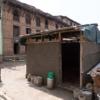 倒壊した自宅の前で笑顔を絶やさないネパール人