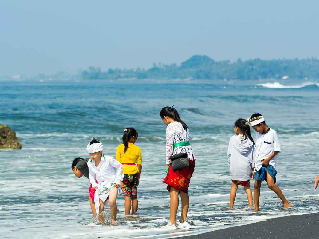 海岸でお清めをする少年少女