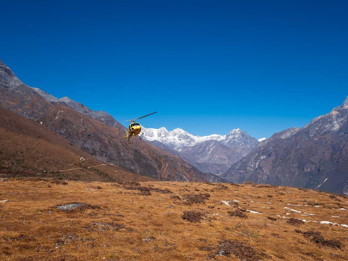 エベレストを背景にしてヘリコプターが到着