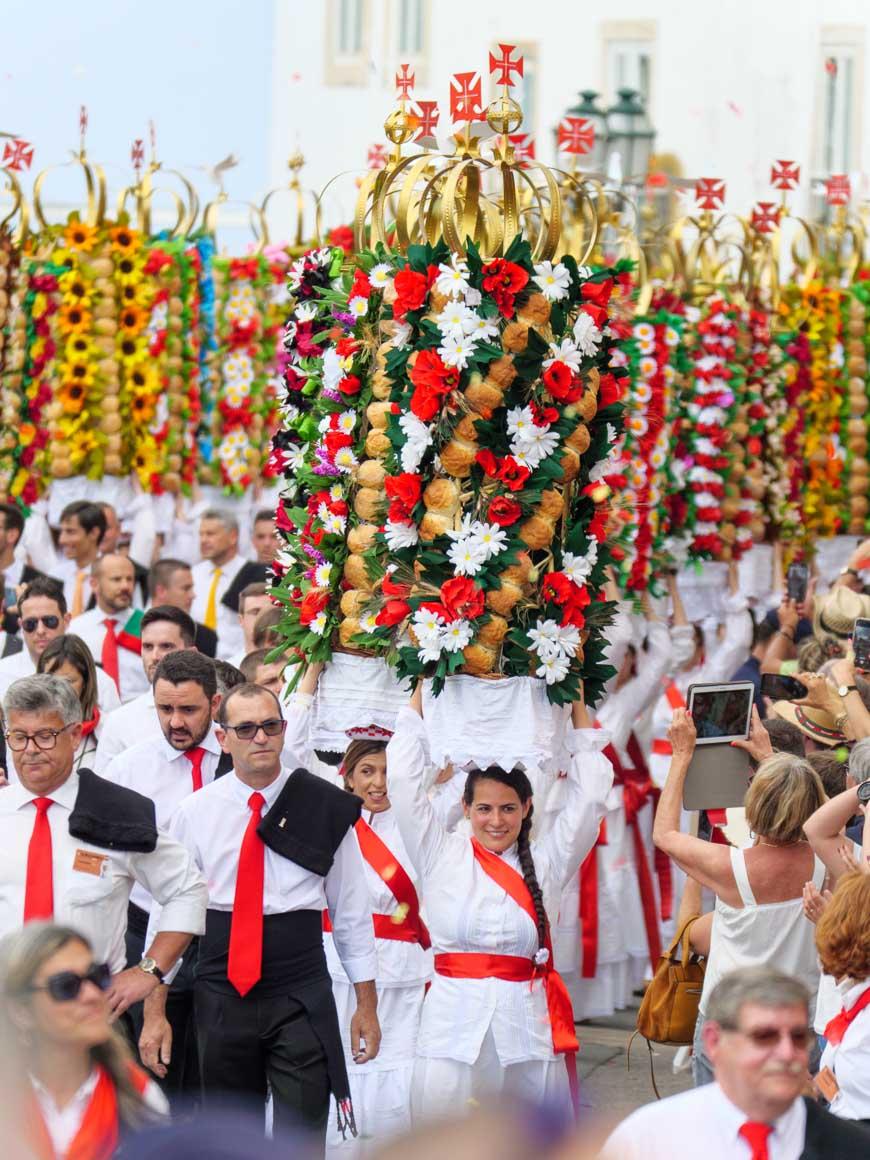 トマールのタブレイロスの祭りでお供えを頭に乗せて歩く女性たち