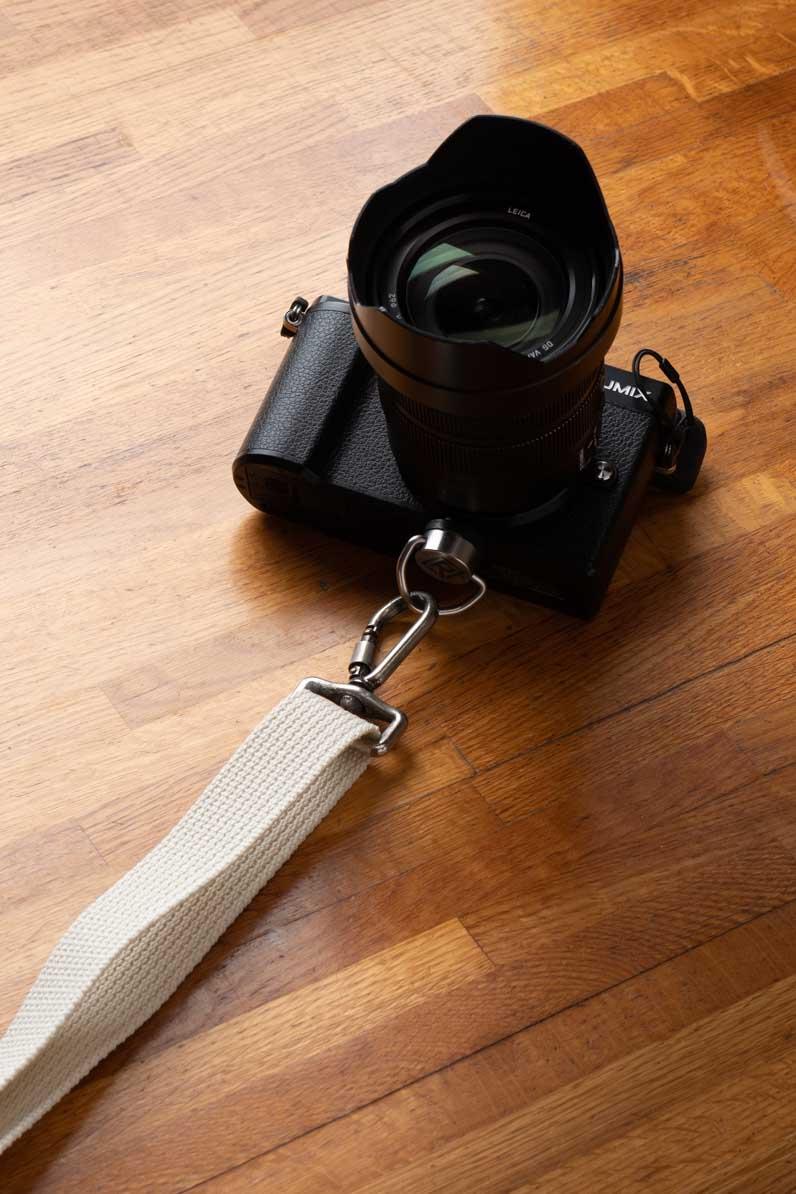 白色のストラップを着けたカメラ